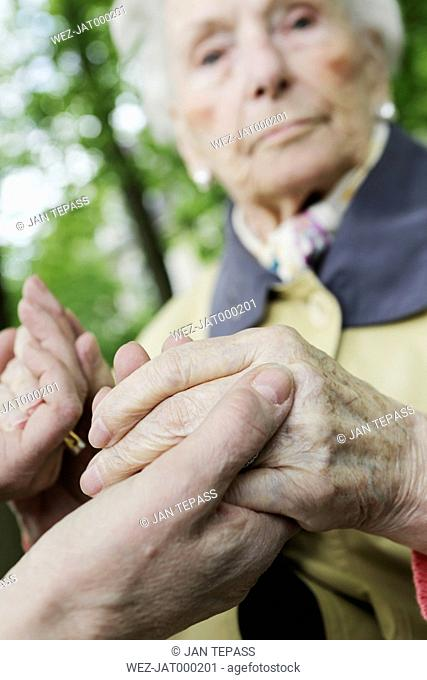 Germany, North Rhine Westphalia, Cologne, Senior woman holding hands of mature woman, close up
