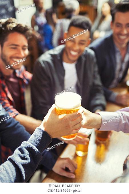 Waiter handing beer to man at bar