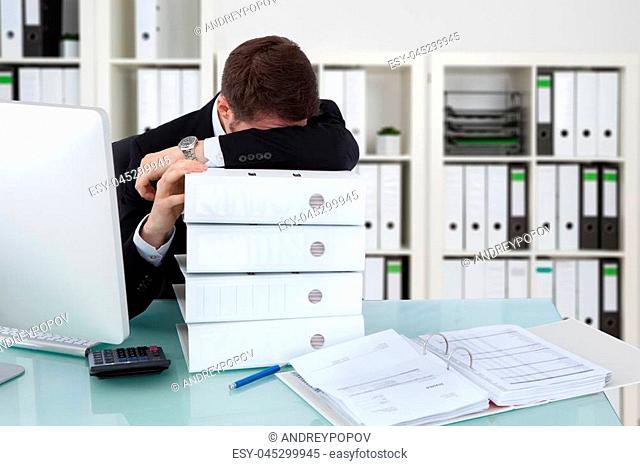 Businessman Sleeping On Stack Of Folders In Office