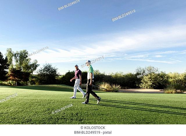Friends walking on golf course