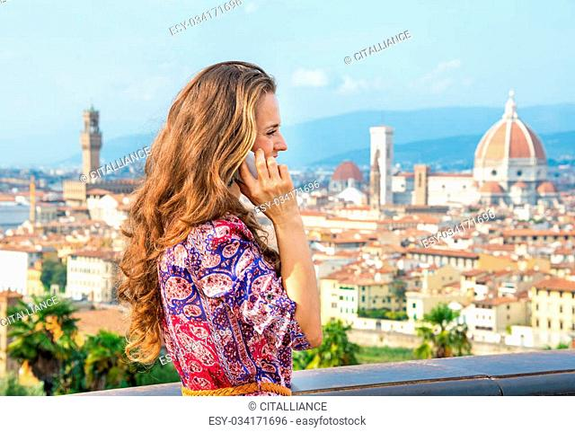 Young woman talking cell phone against panoramic view of florence, italy