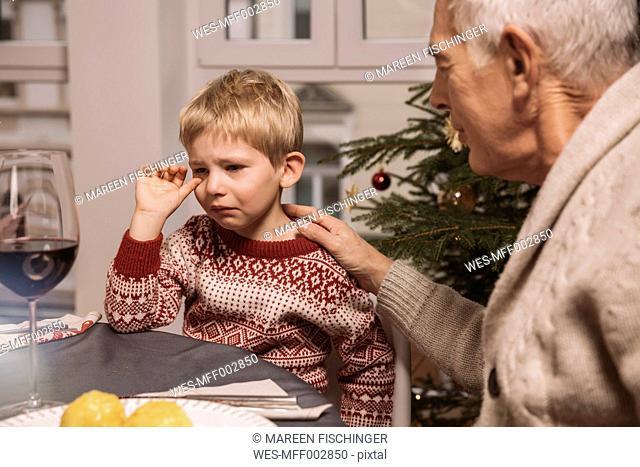 Grandfather comforting sad boy during Christmas dinner