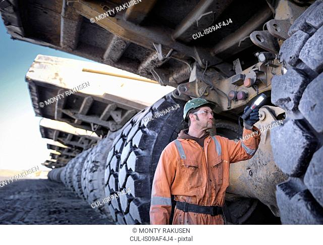 Coal miner inspects dumper truck tyre tread in surface coal mine