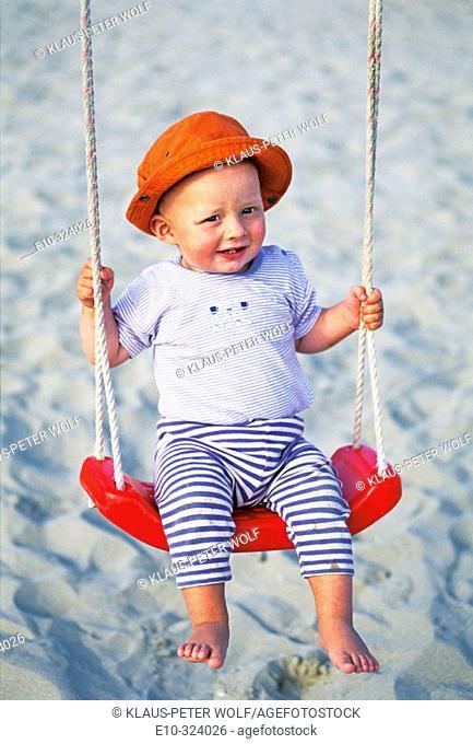Little one year old boy on swing