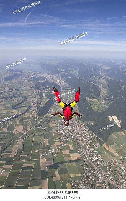 Female skydiver free falling upside down over Grenchen, Berne, Switzerland