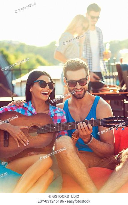 Guitar fun. Joyful young man teaching his girlfriend to play the guitar while two people barbecuing in the background