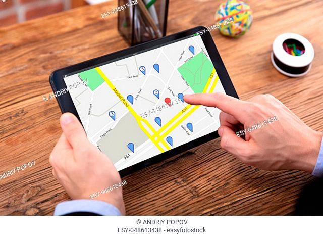 Close-up Of A Person's Hand Using GPS Map With Navigation Pointer On Digital Tablet