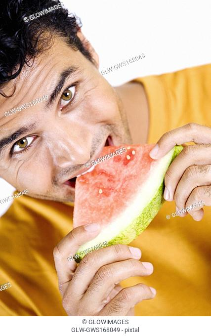 Portrait of a young man eating a slice of a watermelon