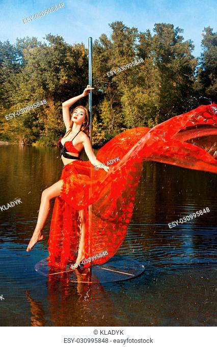 Girl revolves around a pole dancing in a red dress. She dances outdoors in the water