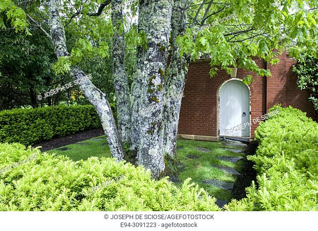 A well designed garden room with trees, shrubs and a white oval toped door in a brick wall