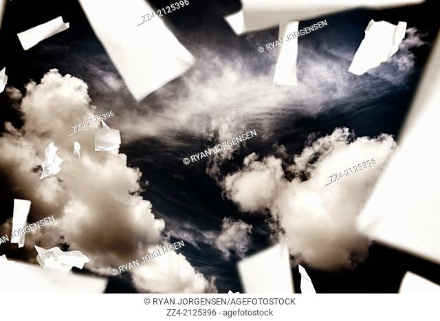 Horizontal image of scrunched, ripped and torn business papers falling in the sky, on cloud background. Report crisis