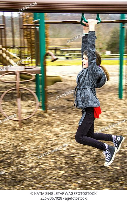 Caucasian beautiful girl wearing a black leggings and white and black jacket. She is in playing in kids playground and going down the Zipline