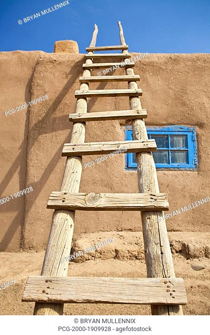 Wooden Ladder Against an Adobe Building