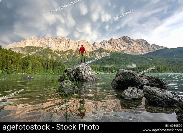 Young man standing on a rock on the shore, Eibsee lake in front of Zugspitze massif with Zugspitze, sunset, dramatic Mammaten clouds, Wetterstein range
