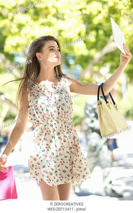 Fashionable woman taking a selfie with digital tablet holding shopping bags