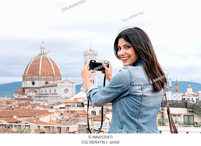 Young woman taking photo of Florence Cathedral and Giotto's Campanile looking over shoulder smiling, Florence, Tuscany, Italy