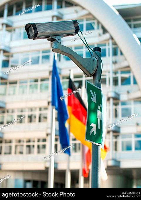 A security camera on a pole with European flags in the background and an emergency gathering point sign