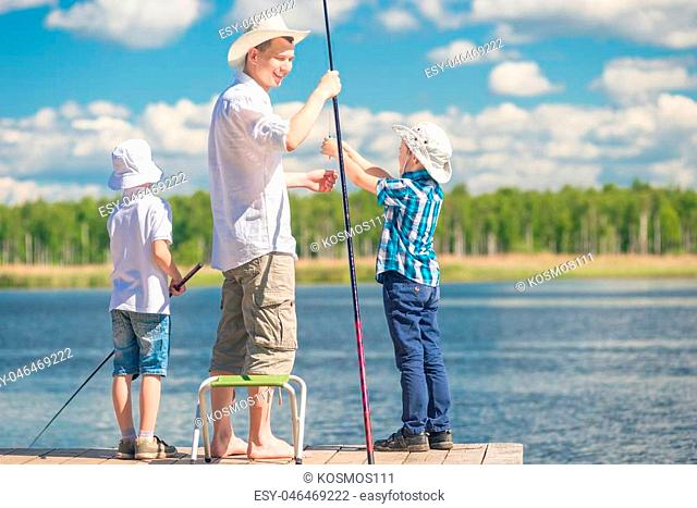 boys with his father on the pier while fishing, holding a weekend concept