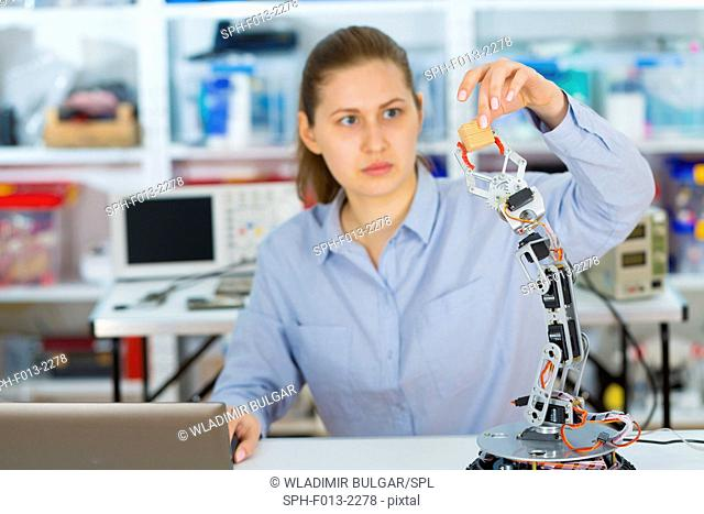 Female electrical engineer working on a robotic arm