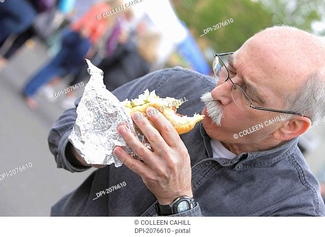Senior man eating a hot dog, troutdale oregon united states of america