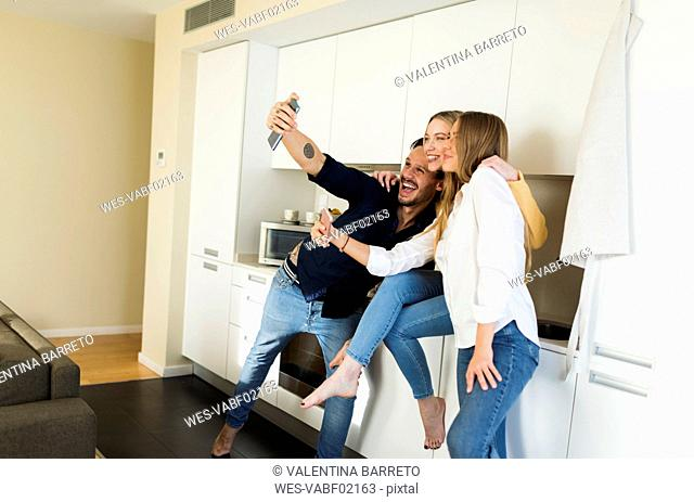 Friends having fun standing in the kitchen, taking pictures with their smartphones