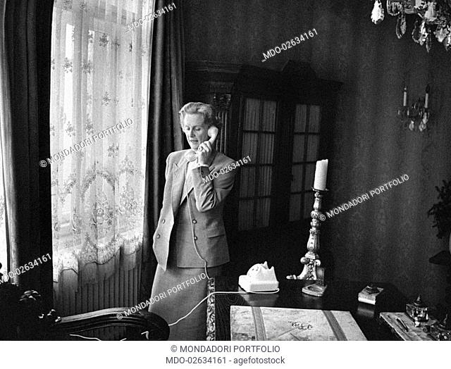 A woman talking on the phone inside her study. Vienna (Austria), November 1955