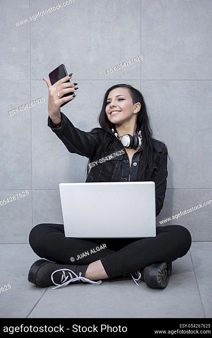 Smiling woman sitting with laptop and taking selfie with smartphone