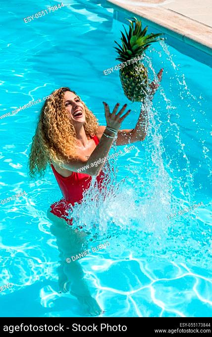Vertical photo of a blonde girl with curly hair and a red swimsuit inside a pool throwing a pineapple in the air creating a water drop wake