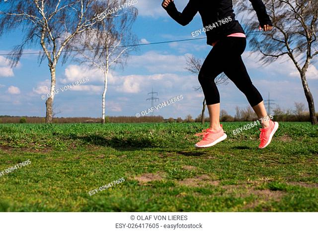 jogger running on a meadow in spring