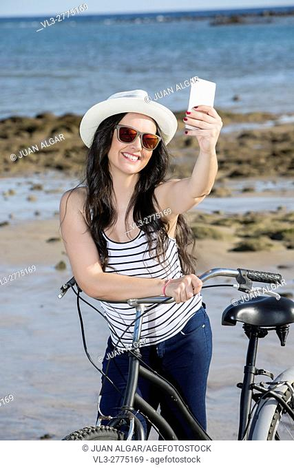 Young smiley woman in hat and sunglasses with bike getting selfie on seaside of Gran Canaria, Spain