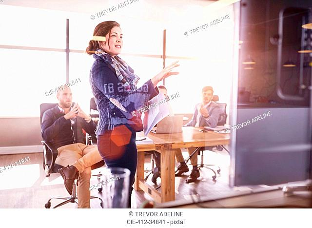 Businesswoman leading meeting at television screen in sunny conference room