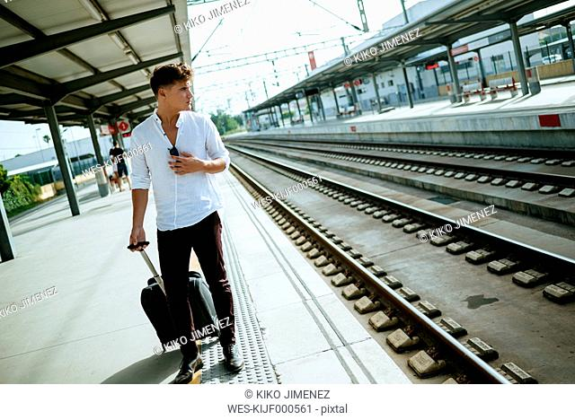 Young man with suitcase waiting at station platform