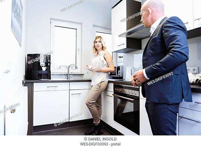 Businessman and businesswoman having coffee break in kitchen