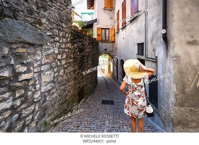 Woman lost in the alleysof Monte Isola on the Iseo Lake, the largest lake island in Europe, Province of Brescia, Lombardy, Italy, Europe