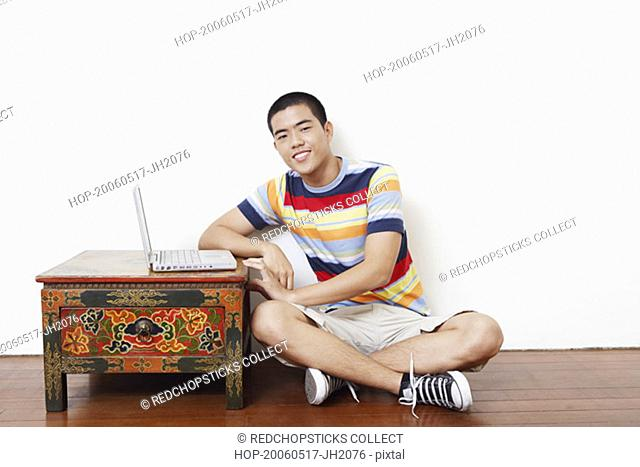 Portrait of a young man sitting on the floor with a laptop on the table