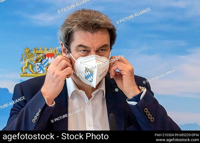 04 March 2021, Bavaria, Munich: Markus Söder (CSU), Minister-President of Bavaria, takes off his protective mask at the beginning of the meeting of the Bavarian...