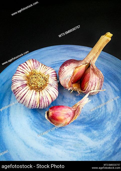 Two purple garlic heads on a blue plate