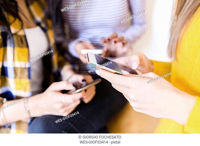 Hands of three women using smartphones