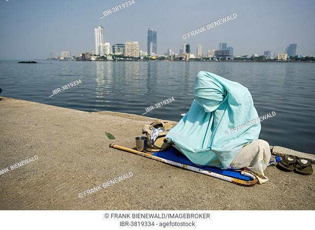 A Muslim woman wearing a burka is begging for money on the walkway, Mahalaksmi, Mumbai, Maharashtra, India