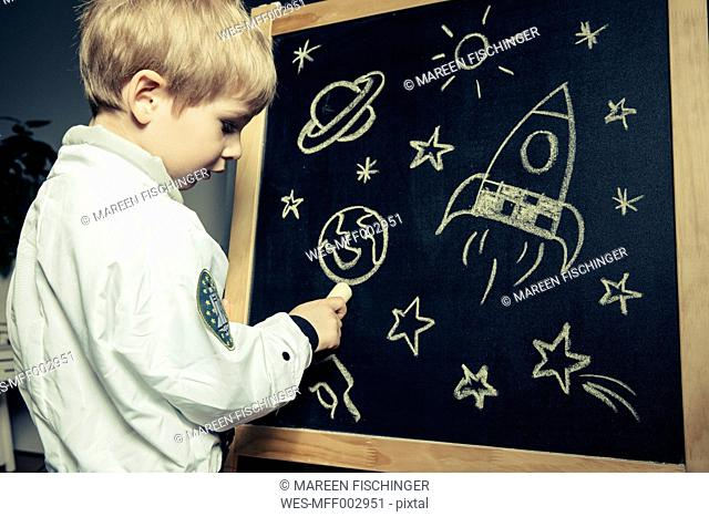 Child with astronaut suit drawing celestial bodies and luminaries onto a chalkboard