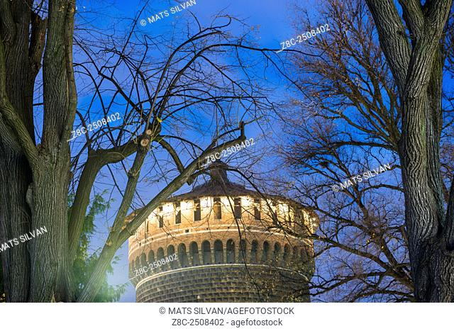 Sforza castle tower with branches in blue hour in Milan, Italy