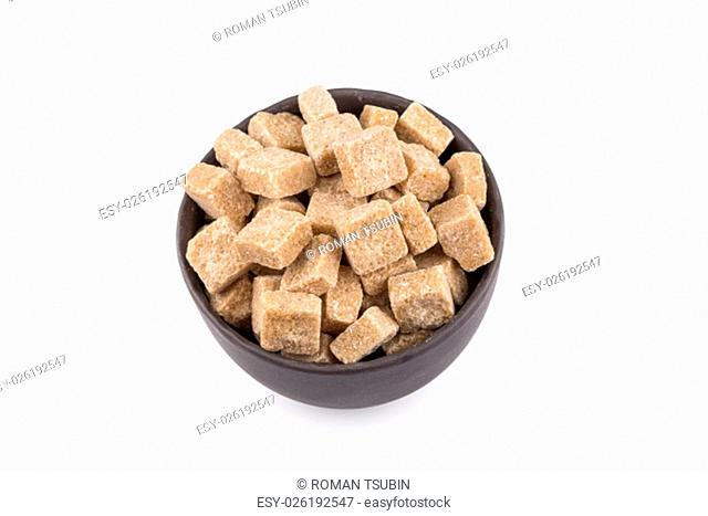 Cubes of whole cane sugar in bowl, isolated on the white background