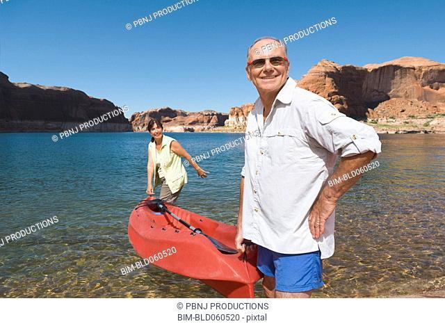 Multi-ethnic senior couple carrying kayak