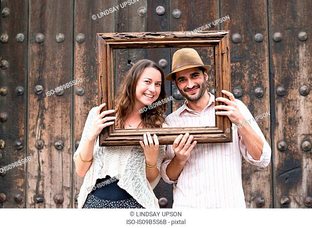 Portrait of mid adult couple, holding wooden frame in front of their faces, Mexico City, Mexico