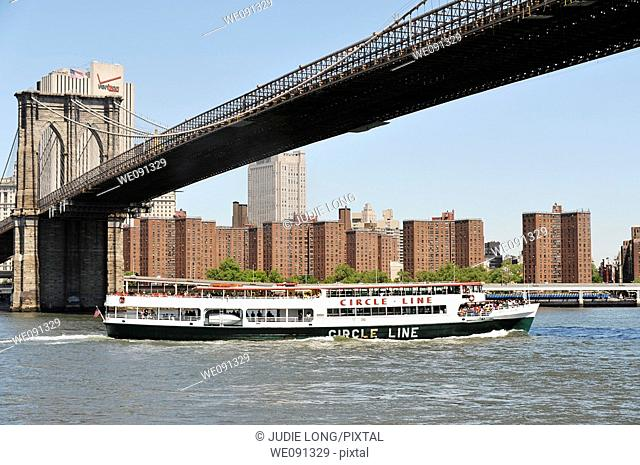 Circle Line Sightseeing Boat passing under the Brookllyn Bridge, New York City, USA