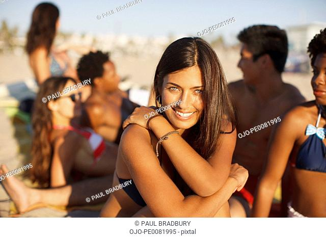 Woman sitting with friends on beach