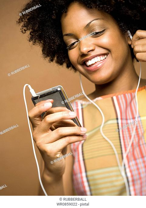 Close-up of a young woman listening an MP3 player
