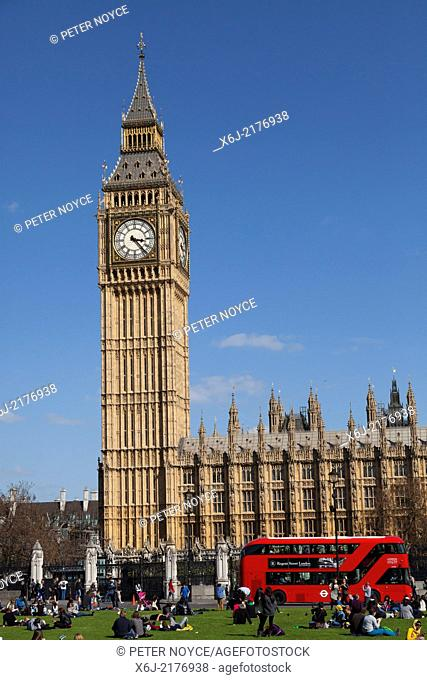 Tourists sitting on the grass of Parliament Square with Big Ben and the Houses of Parliament London
