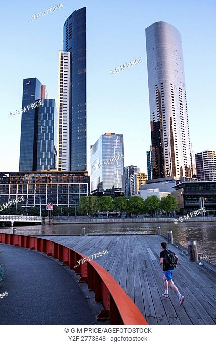 Man jogging on Enterprise Wharf with view of Southbank skyline, Melbourne