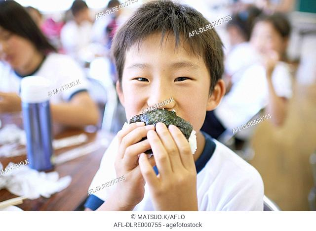 Japanese elementary school kid eating in the classroom
